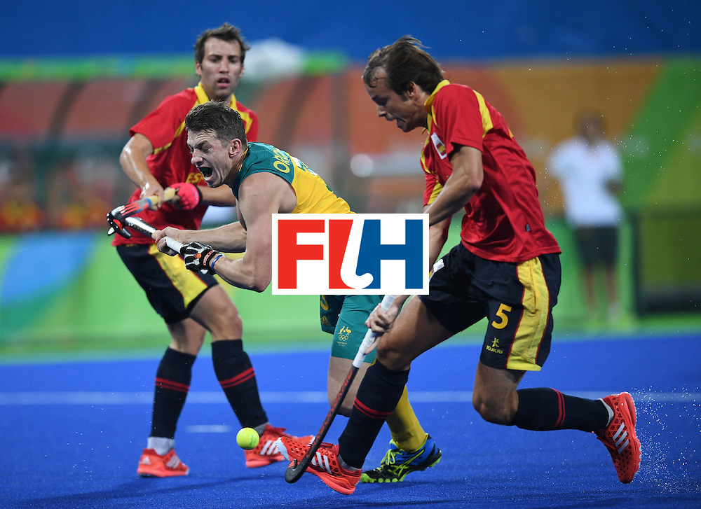 Australia's Simon Orchard (C) falls between Spain's Sergi Enrique (L) and Bosco Perez-Pla  during the men's field hockey Australia vs Spain match of the Rio 2016 Olympics Games at the Olympic Hockey Centre in Rio de Janeiro on August, 7 2016. / AFP / MANAN VATSYAYANA        (Photo credit should read MANAN VATSYAYANA/AFP/Getty Images)