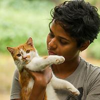 Fishing Cat (Prionailurus viverrinus) biologist, Anya Ratnayaka, holding Domestic Cat (Felis catus), Urban Fishing Cat Project, Colombo, Sri Lanka