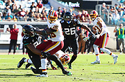 Dec 16, 2018; Jacksonville, FL, USA; Washington Redskins running back Adrian Peterson (26) tries to break a tackle by Jacksonville Jaguars defensive tackle Calais Campbell (93) during an NFL game at TIAA Bank Field. The Redskins beat the Jaguars 16-13. (Steve Jacobson/Image of Sport)