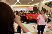 Opening weekend of posh Siam Paragon shopping center. Visitors taking souvenir photos with luxury cars, here a Ferrari Enzo..