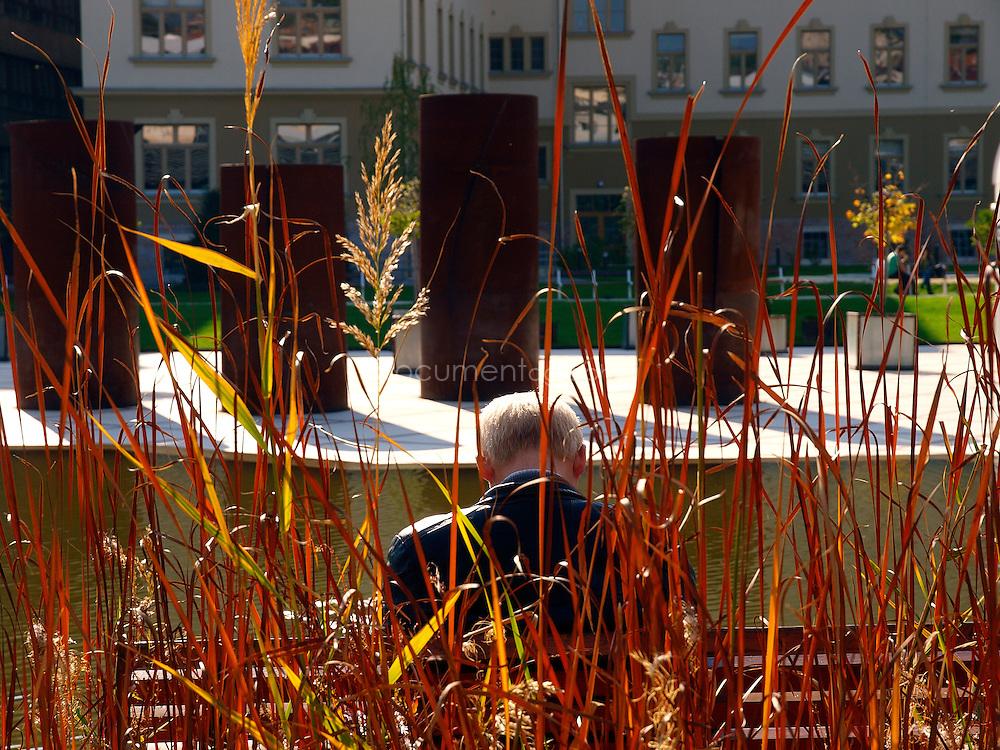 A man rests near the pond at the Millenáris Fogadó, Budapest, Hungary.