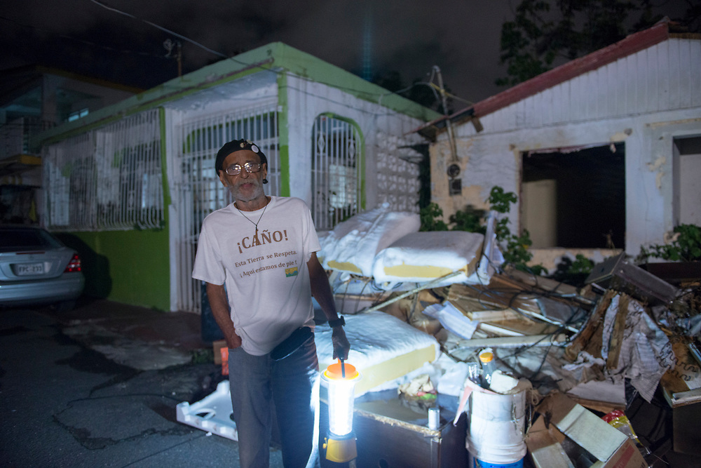 San Juan, PR November 8, 2017 -- Joe Caraballo Diaz and his wife Janet Diaz Santiago sit in their home using solar lamps in the Barrio Obrero Marina neighborhood in San Juan, PR. Joe is a grassroots activist and community organizer with G-8, Inc., a nonprofit that organizes the residents of the eight communities situated along the Caño Martín Peña. Photo by Lori Waselchuk/braf.org
