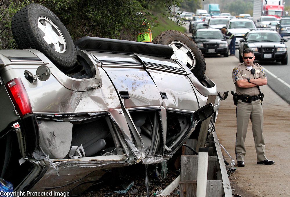 California Highway Patrol officer Grant Boles inspects a GMC SUV that rolled over on Highway 17 south of Mount Hermon Road in Scotts Valley, California on Thursday March 27, 2014. The driver and both passengers in the vehicle sustained injuries in the crash.<br />Shmuel Thaler / Santa Cruz Sentinel