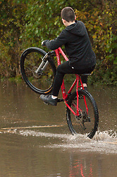 © Licensed to London News Pictures. 16/11/2019. Tewkesbury, Worcestershire, UK. A young lad rides his bike through a flooded road on the outskirts of Tewkesbury in Worcestershire. Many roads around Tewkesbury are seriously flooded. After several days of heavy rainfall, there is severe flooding in many parts of  Worcestershire, UK. Levels are expected to peak this afternoon.  Photo credit: Graham M. Lawrence/LNP