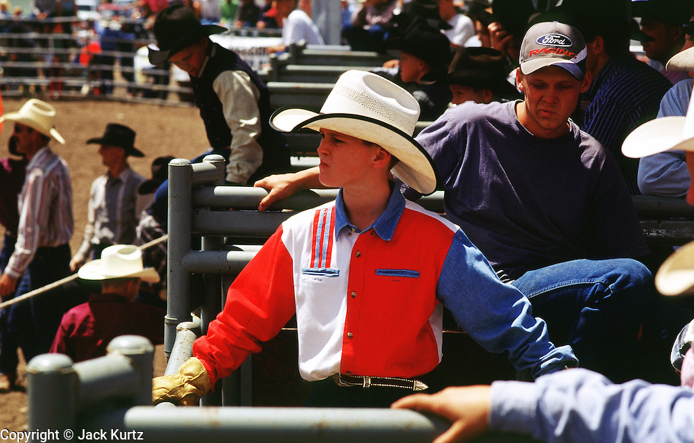 05 AUGUST 2000 - WILLIAMS, AZ: zYoung cowboys watch the action to begin at the 22nd Annual Cowpunchers' Reunion Rodeo in Williams, Arizona, Aug 5.  The Cowpunchers' Reunion Rodeo is held for working cowboys from the ranches in Arizona and the region. PHOTO BY JACK KURTZ