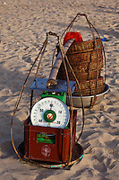 Fishing baskets and scales on the beach.