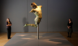 © Licensed to London News Pictures. 11/09/2012. LONDON, UK. Two members of Royal Academy of the Arts staff look at the 2000 year old 'Dancing Satyr' at the academy's latest exhibition entitled 'Bronze' in London today (11/09/12). The Satyr, discovered off the coast of Sicily in 1998 is considered one of the greatest of all classical bronzes, forms the signature piece for the exhibition that runs from 15 September to 9 December 2012. Photo credit: Matt Cetti-Roberts/LNP