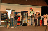 L-R: Bob Sheeks (DARK TEE SHIRT), owner of Dani's Auto, which adjoins the Xtra gas station where a station attendant was murdered, Laurel Springs Police Chief George Kralley (LIGHT JACKET, AND DARK CAP), and area resident Rob McPherson outside the station where the murder took place. Chief Kralley was guarding the crime scene on the White Horse Pike in Laurel Springs, NJ., waiting for detectives to return to the scene for further investigation. On the far right are friends and family of the murder victim.