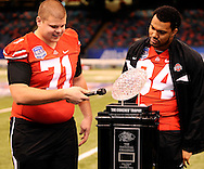 Ohio State's Steve Rehring, left, has a laugh as he pretends to interview the National Champion Coaches' Trophy on Media Day at the Superdome in New Orleans, Jan. 5, 2007. Looking on is Doug Worthington.