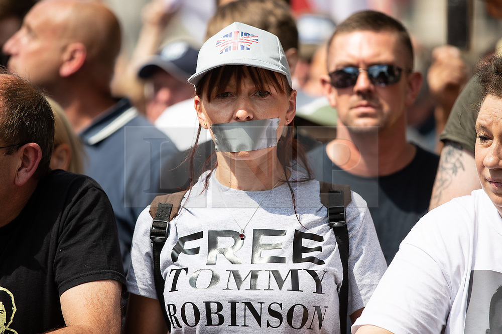 """© Licensed to London News Pictures. 14/07/2018. London, UK. A woman with her mouth taped over . Supporters of EDL founder Tommy Robinson ( real name Stephen Yaxley-Lennon ) and US President Donald Trump hold a """" Welcome Trump """" rally on Whitehall . Trump is currently in Scotland and Robinson is in HMP Hull . Photo credit: Joel Goodman/LNP"""
