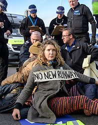 "© Licensed to London News Pictures. 19/11/2016. Heathrow, UK. An activist reported to be SOPHIE LYSACZANKO , wearing the slogan ""NO NEW RUNWAY"" sits on the road surface, that she and other activists are attached to, near Heathrow Airport. A group of activists stage attach themselves to a road surrounding  Heathrow Airport, during a demonstration against the expansion of Heathrow Airport and the building of a third runway. Some activists  threatened ""direct action"". Photo credit: Ben Cawthra/LNP"