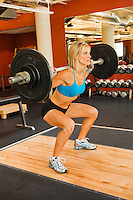 A physically fit woman doing squats in a health club weight room.