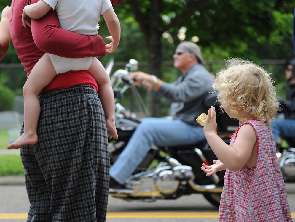 Laura Fong - A young mother and her two children wave to the men and women on motorcycles in the annual Alcoholics Anonymous Founders' Day motorcade.