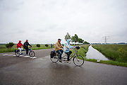 Een stel op een elektrische tandem en een stel op een toertandem passeren de wielanden. Bij Utrecht wordt de tandemtocht gehouden. De tocht werd van 1975 tot 1982 jaarlijks gehouden en was in die tijd een groots succes. Organisator Herbert Kuner, een expert in oude fietsen, wil het nu nieuw leven inblazen. In totaal rijden dit jaar vijftien tandems mee. Tijdens de route van 40km rondom Utrecht hoeven de fietsers slechts zes verkeerslichten te passeren.<br /> <br /> In Utrecht, the tandem tour is held. The tour was held annually from 1975 to 1982 and at that time was a grand success. Organizer Herbert Kuner, an expert in old bikes, wants to restart the tradition. In total this season, with fifteen tandems. During the route of 40km around and Utrecht cyclists passing only six traffic lights.