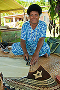 Fijian woman painting design on tapa cloth; Tongo village,  Qamea Island, Fiji.