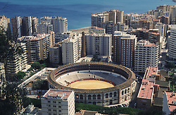 View of Malaga showing bullring and tower blocks with sea in background,