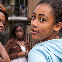 A group of African-American teenage girls. One girl glances over her shoulder at the camera and another has a cell phone to her ear while looking towards the camera.