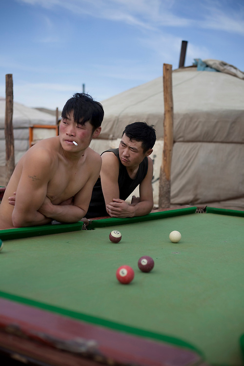 Badamgarav, in black and Byambasuren, shirtless, pass the hours playing pool in a ger camp at the edge of a gold mine in Uyanga, Mongolia. Gold fever is breeding a new kind of nomad, those who roam in search of gold instead of to care for livestock.