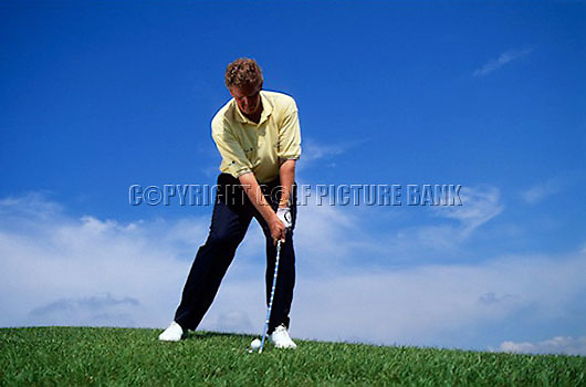Colin Montgomerie down hill chip shot technique. Wider stance. Ball played towards front foot almost in line with inside heel of left foot. Steep backswing. Stay down and through the shot after impact.<br /> EDITORIAL USE ONLY-NO MODEL RELEASE.