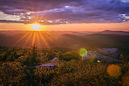 The clouds appear like a curtain closing over the sky with the sun bathing the mountains and valleys with its warm rays one last time before descending below the horizon.  Taken from the top of Spruce Knob in West Virginia.