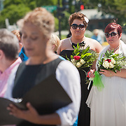 Liberty Manos, center and partner, Shannon Glatz, both of Akron, Ohio, listen as Officiant, Tiffany Newman, left, marries twenty-five gay couples in front of the Supreme Court of the United States, on June 21, 2013.  The couples traveled to Washington on the C-Bus of Love to get married en masse the week before decisions are expected to be made on the Defense of Marriage Act (DOMA) and Proposition 8.