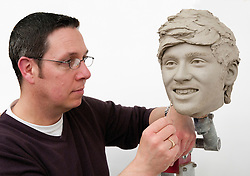 """© Licensed to London News Pictures. 15/02/2013. London, UK Sculptor Stephen Mansfield works on the clay head of Zayn Malik. Madame Tussauds today released pictures of sculptors working on the life-like clay heads of the five members of pop band """"One Direction ' The clay heads will be used to create the moulds for their new wax figures. Niall, Liam, Louis, Harry and Zayn have been closely involved in the creation process giving the creative team two sittings at which hundreds of measurements were taken to ensure total accuracy. The clay heads will now be used to make the moulds for the final wax figures, which will be revealed in London. Photo credit : Madame Tussauds /LNP"""