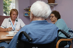 Occupational Therapist talking to amputee patient and his wife about his home care arrangements,