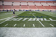 Players warm up near an NFL Play Football logo painted on the field before the Los Angeles Rams 2016 NFL preseason football game against the Dallas Cowboys on Saturday, Aug. 13, 2016 in Los Angeles. The Rams won the game 28-24. (©Paul Anthony Spinelli)