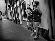 Sex workers take a break outside their street front, glass-doored booths.  Groningen, The Netherlands.  Although prostitution is legal in the Netherlands, young men of Eastern European origin stand guard at the ends of alleyways carefully watching the activities of the young women.  Although the nationalities of these particular women are not known, many of the sex workers in the Netherlands are from Eastern Europe.