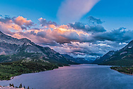 Sunset clouds over Upper Waterton Lake from the Prince of Wales Hotel viewpoint on a very windy evening! With a few fast-moving cumulus clouds catching the setting sunlight.<br /> <br /> With the 24mm Sigma lens and Nikon D750. Taken as part of a 700-frame motion-control time-lapse.
