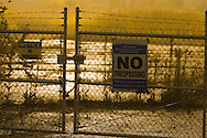 "A ""No Trespassing"" sign on a foggy night in an urban setting."
