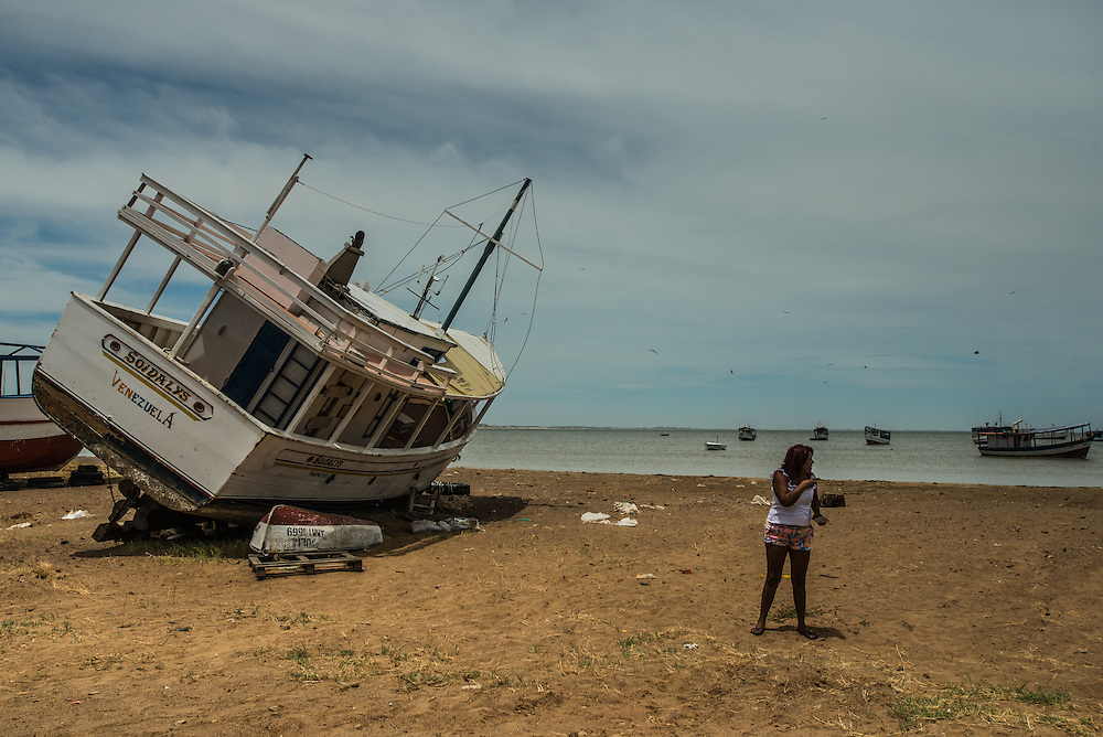 LA VELA, VENEZUELA - SEPTEMBER 22, 2016: Maria Pi&ntilde;era walks on the beach to meet with a smuggler to discuss when they are leaving. To escape the crisis, Ms. Pi&ntilde;era spent all of her savings to pay smugglers to take her in a small fishing boat to Curacao island. &ldquo;I&rsquo;m nervous,&rdquo; she said. &ldquo;I&rsquo;m leaving with nothing. But I have to do this. Otherwise, we will just die here hungry.&rdquo;<br /> Despite having the largest known oil reserves in the world, Venezuela is suffering from hyperinflation and a severe economic crisis making affordable food difficult for most middle and working class families to access.  Well over 150,000 Venezuelans have fled the country in the last year alone, the highest in more than a decade, according to scholars studying the exodus. As Hugo Ch&aacute;vez&rsquo;s Socialist-inspired revolution collapses into economic ruin, as food and medicine slip further out of reach, the new migrants include the same impoverished people that Venezuela&rsquo;s policies were supposed to help. &ldquo;We have seen a great acceleration,&rdquo; said Tom&aacute;s Paez, a professor who studies immigration at the Central University of Venezuela. He says that as many as 200,000 Venezuelans have left in the last year, driven by how much harder it is to get food, work and medicine &mdash; not to mention the crime such scarcities have fueled.  PHOTO: Meridith Kohut for The New York Times