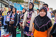 "15 JANUARY 2014 - BANGKOK, THAILAND: Thai Muslim women sing the Thai national anthem at the main stage for Shutdown Bangkok. Wednesday morning prayers were led by Buddhist monks, Muslim imams and a Catholic priest. Tens of thousands of Thai anti-government protestors continued to block the streets of Bangkok Wednesday to shut down the Thai capitol. The protest, ""Shutdown Bangkok,"" is expected to last at least a week. Shutdown Bangkok is organized by People's Democratic Reform Committee (PRDC). It's a continuation of protests that started in early November. There have been shootings almost every night at different protests sites around Bangkok. The malls in Bangkok are still open but many other businesses are closed and mass transit is swamped with both protestors and people who had to use mass transit because the roads were blocked.    PHOTO BY JACK KURTZ"