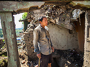 03 AUGUST 2015 - SANKHU, NEPAL:  A laborer looks at a home he was hired to demolish in Sankhu, a community about 90 minutes from central Kathmandu. The home was damaged in the earthquake and the owners hope to rebuild on the site but first half to take down what's left of the existing home. The Nepal Earthquake on April 25, 2015, (also known as the Gorkha earthquake) killed more than 9,000 people and injured more than 23,000. It had a magnitude of 7.8. The epicenter was east of the district of Lamjung, and its hypocenter was at a depth of approximately 15 km (9.3 mi). It was the worst natural disaster to strike Nepal since the 1934 Nepal–Bihar earthquake. The earthquake triggered an avalanche on Mount Everest, killing at least 19. The earthquake also set off an avalanche in the Langtang valley, where 250 people were reported missing. Hundreds of thousands of people were made homeless with entire villages flattened across many districts of the country. Centuries-old buildings were destroyed at UNESCO World Heritage sites in the Kathmandu Valley, including some at the Kathmandu Durbar Square, the Patan Durbar Squar, the Bhaktapur Durbar Square, the Changu Narayan Temple and the Swayambhunath Stupa. Geophysicists and other experts had warned for decades that Nepal was vulnerable to a deadly earthquake, particularly because of its geology, urbanization, and architecture.    PHOTO BY JACK KURTZ