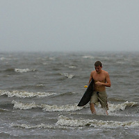 A surfer heads out of the waters off the coast of Cedar Key, Florida after trying to catch some waves generated by Tropical Storm Alberto June12, 2006. REUTERS/Scott Audette