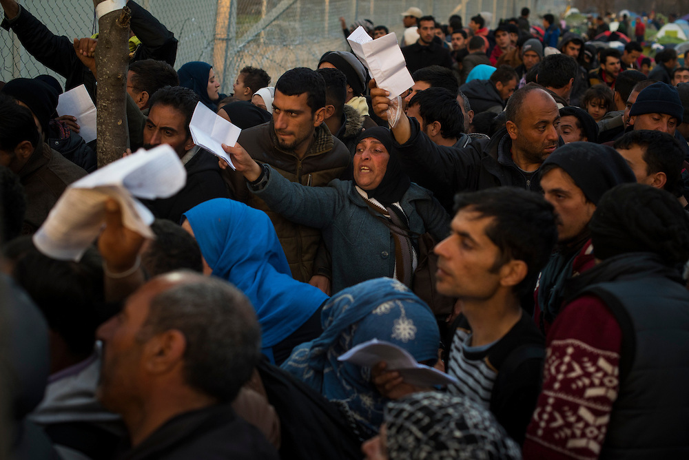 Refugees hold up their papers in the hopes that they'll be one of the approximately 50 let into Macedonia at a refugee camp on the Macedonian border on March 6, 2016 in Idomeni, Greece.