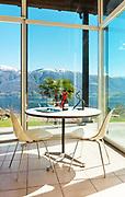 aperitif on the veranda, interior of a mountain home, lake view