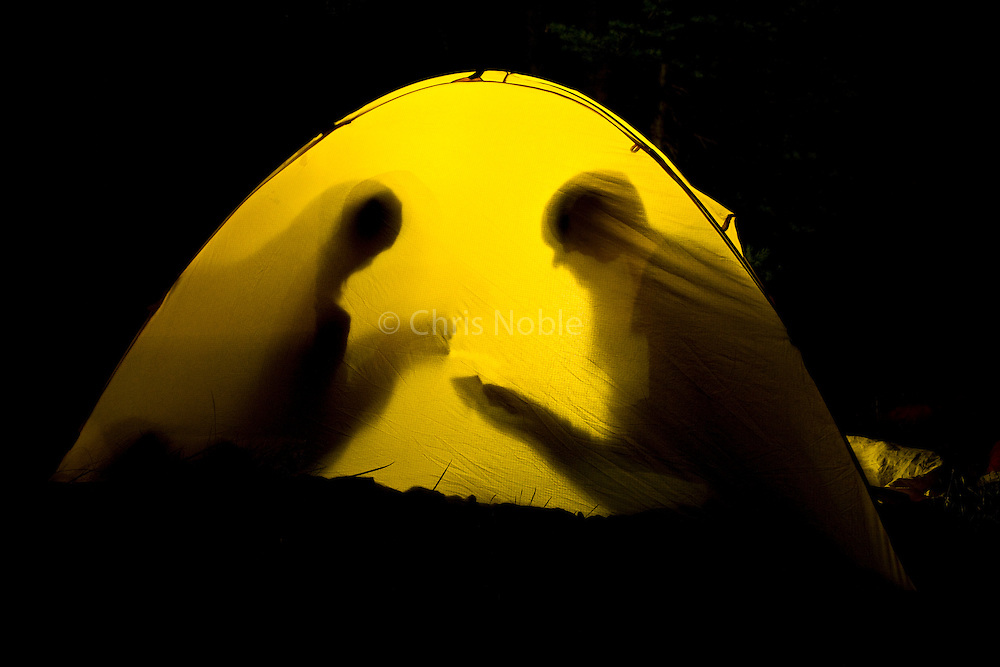 Two women, silhouetted against the exterior of their tent, enjoy a nighttime game of cards during a camping trip to Lily Lake, in Utah's Uinta Mountains.