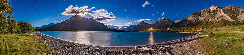 A photographer, at far right, is shooting a moonlit nightscape at Driftwood Beach, at Waterton Lakes National Park, Alberta. The nearly Full Moon, here partly obscured by clouds at left above Vimy Peak, provides the illumination. The sky is blue with moonlight but contains stars, plus bright Mars and Saturn above the Prince of Wales Hotel. <br /> <br /> This is a stitch of 8 panels (all about 6 second exposures), plus two additional panels with shorter exposures (1 second), blended in to provide more detail in the bright moonlit clouds and glitter path from the Moon. All with the 24mm lens at f/2.8 and Nikon D750 at ISO 1600. Stitched with Adobe Camera Raw.