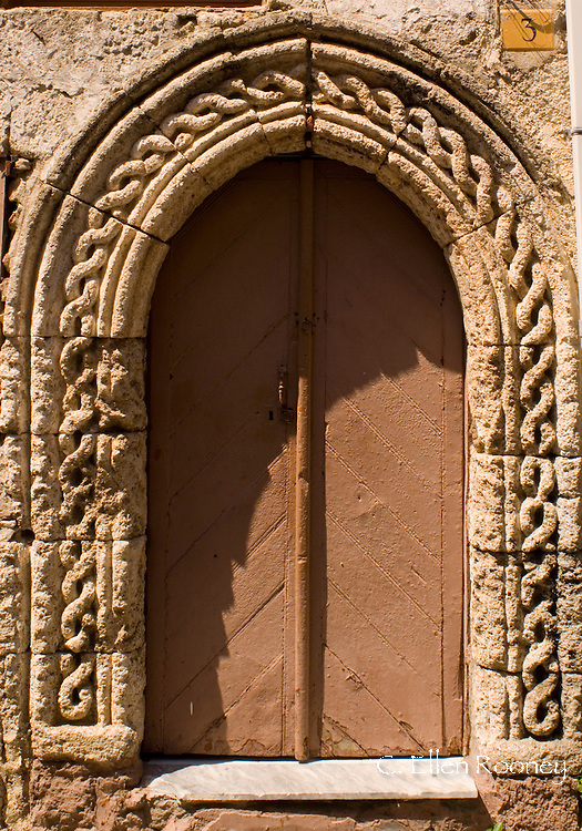 An old door with carved stone work in Rhodes Town, Rhodes, Dodecanese Islands,<br /> Greece