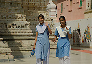 Two school girls in blue and white uniforms outside a temple in Udaipur, Rajasthan, India