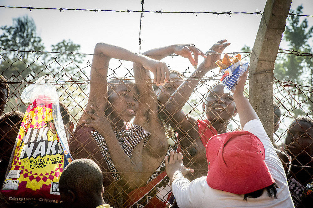Ludzidzini, Swaziland, Africa - Annual Umhlanga, or reed dance ceremony, in which up to 100,000 young Swazi women gather to celebrate their virginity and honor the queen mother during the 8 day long event.<br /> Maidens purchase snacks from across fence