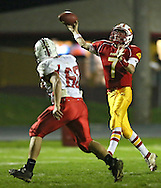 Marion's Trevor Hardman (7) throws a touchdown pass as Western Dubuque's Sean Wagner (60) closes in during their first round playoff game at Thomas Park Field in Marion on Wednesday, October 24, 2012.