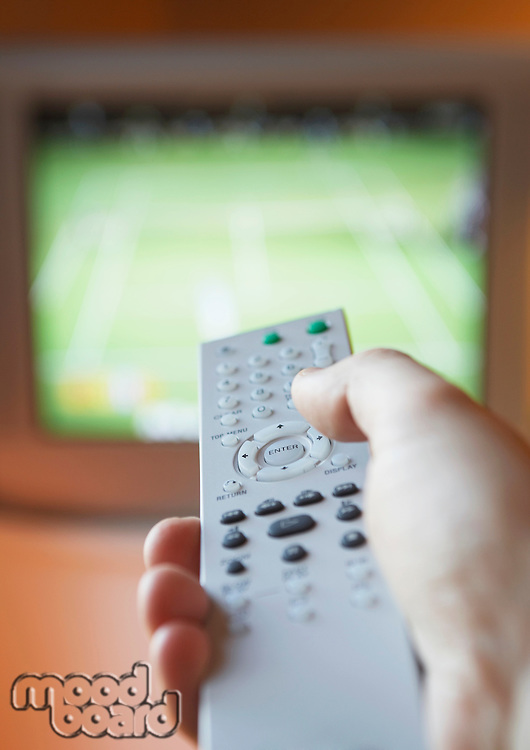 Man adjusting TV channel volume with remote control close-up of hand