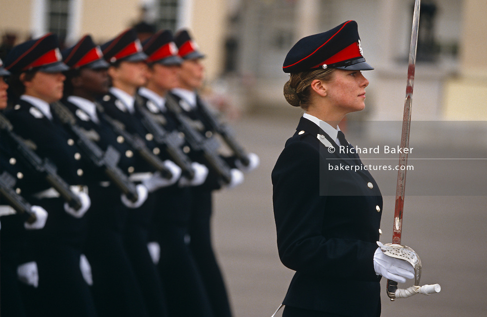 Female officer cadets march in line with their weapons on shoulders past guests and VIPs at their passing out parade in the Royal Military Academy Sandhurst. An honoured cadet strides in front holding a ceremonial sword vertically in her white glove while one cadet in the main line-up is of an ethnic minority. The Royal Military Academy Sandhurst (RMAS), commonly known simply as Sandhurst, is the British Army officer initial training centre. Sandhurst is prestigious and has had many famous alumni including Sir Winston Churchill, King Abdullah II of Jordan, Sultan Qaboos of Oman and, more recently, Prince Harry and Prince William. All British Army officers, and many from elsewhere in the world, are trained at Sandhurst. RMA Sandhurst was formed in 1947, from a merger of the Royal Military Academy in Woolwich (which trained officers for the Royal Artillery and Royal Engineers from 1741 to 1939) and the Royal Military College at Sandhurst.