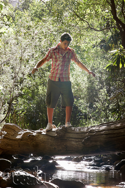 Young Man Balancing on Log