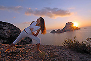 Attractive woman practicing yoga in Ibiza