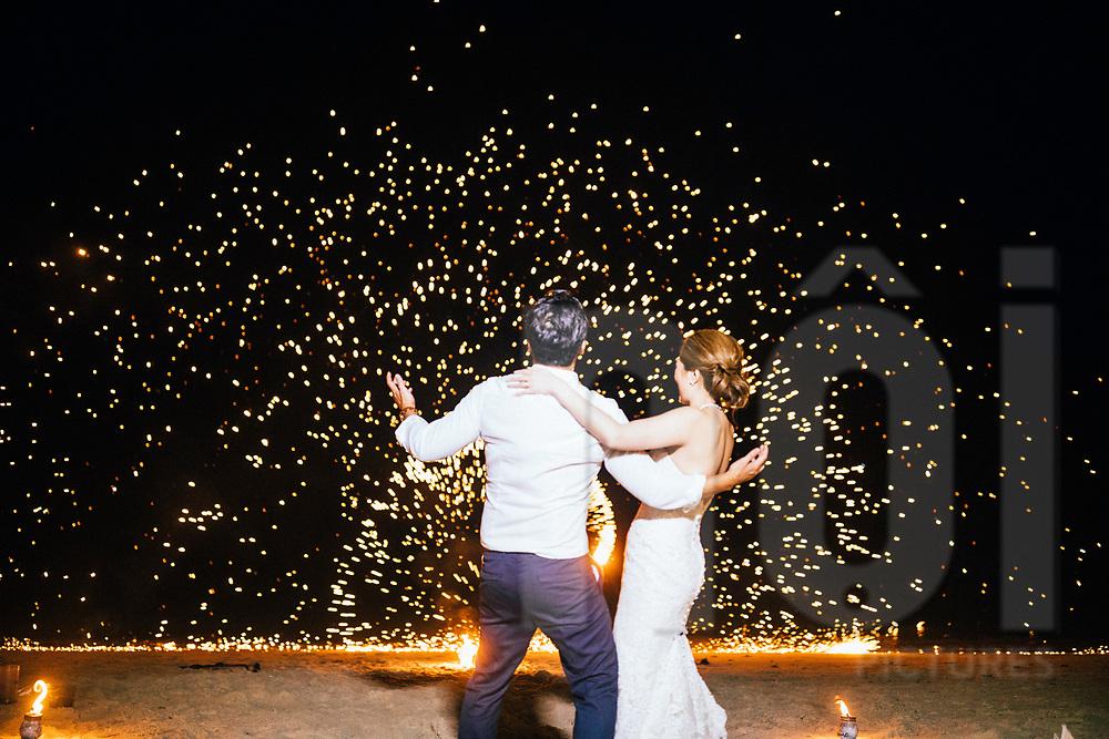 A fire dancer performs for a bride and groom at a beach wedding, Ko Samui, Thailand, Southeast Asia