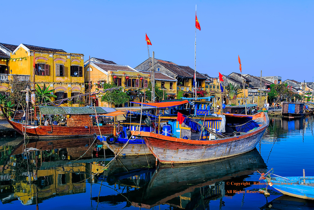 An aquatic view of down town Hoi An riverside, with the characteristic colonial styled yellow buildings and the boats at harbour, Hoi An Vietnam.