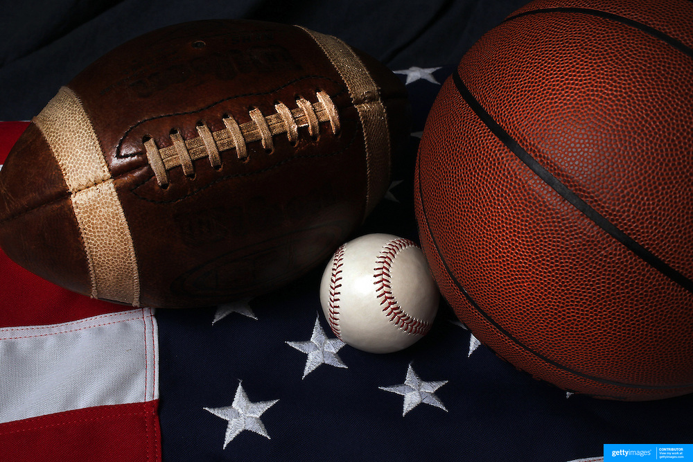 A studio shot of an American Football, a baseball, and a basketball and a USA flag. 17th October 2012. Photo Tim Clayton